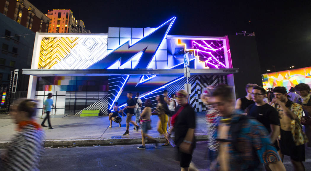 Attendees pass by a neon installation during the third day of the annual Life is Beautiful festival in downtown Las Vegas on Sunday, Sept. 23, 2018. Chase Stevens Las Vegas Review-Journal @cssteve ...