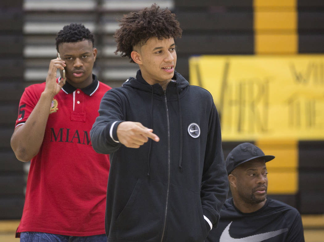 Clark senior Jalen Hill, middle, talks with friends during an event to announce his commitment to play basketball at the University of Oklahoma on Thursday, Sept. 20, 2018, at Clark High School, i ...