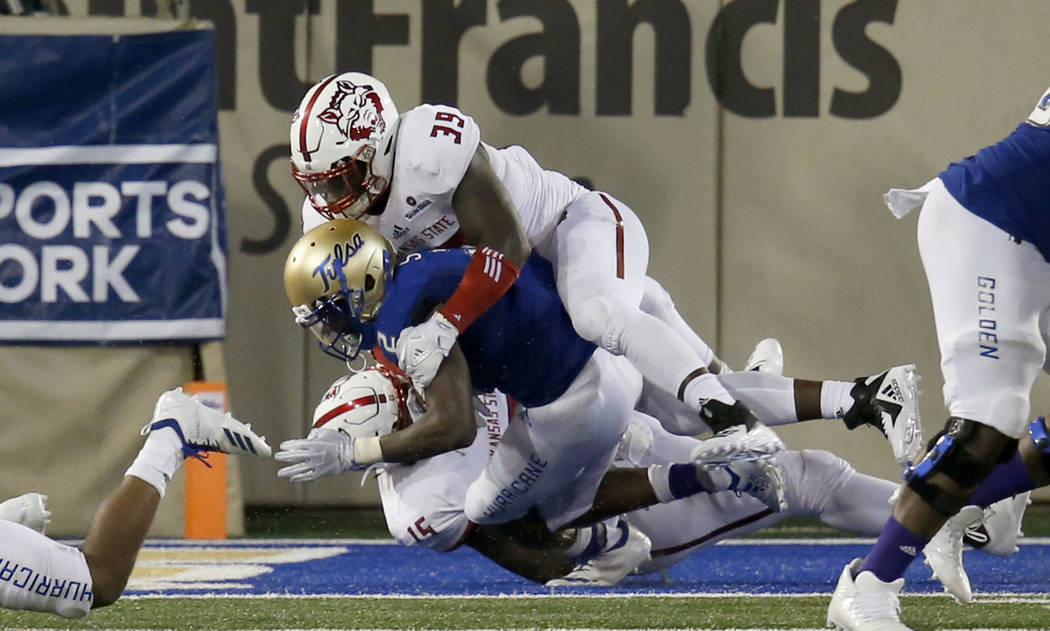 Tulsa's Keylon Stokes is tackled for a safety by Arkansas State's Kevin Thurman and Dajon Emory during an NCAA college football game, Saturday, Sept. 15, 2018 in Tulsa, Okla. (Stephen Pingry/Tulsa ...