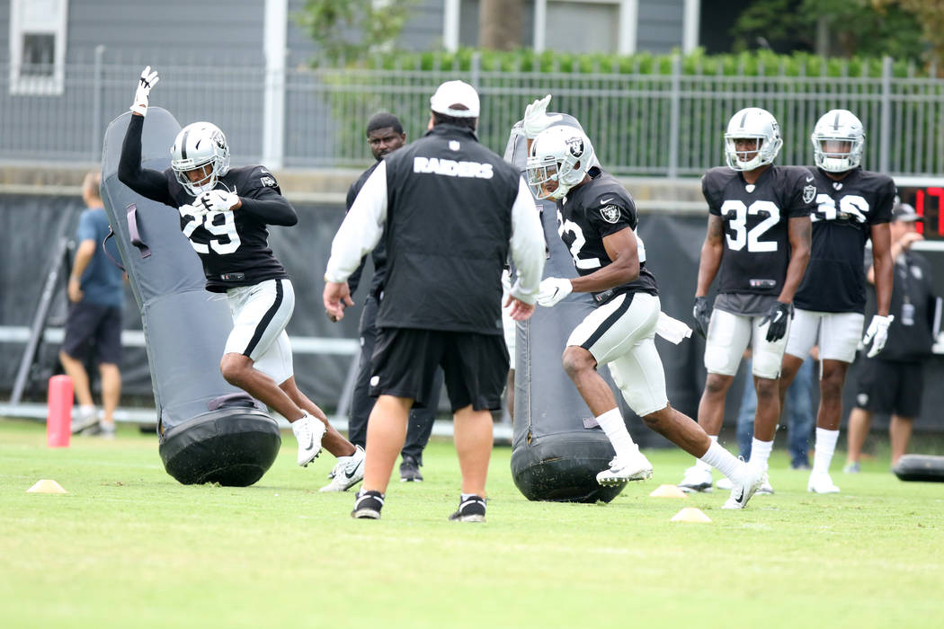 Oakland Raiders defensive backs Leon Hall (29) and Rashaan Melvin (22) brush by tackle posts as cornerbacks Antonio Hamilton (32) and Daryl Worley (36) wait to drill at the team's NFL training cam ...