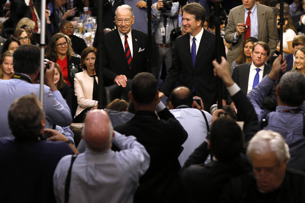 Supreme Court nominee Judge Brett Kavanaugh is surrounded by photographers as he stands with Senate Judiciary Committee Chairman Chuck Grassley R-Iowa, during his confirmation hearing on Capitol H ...