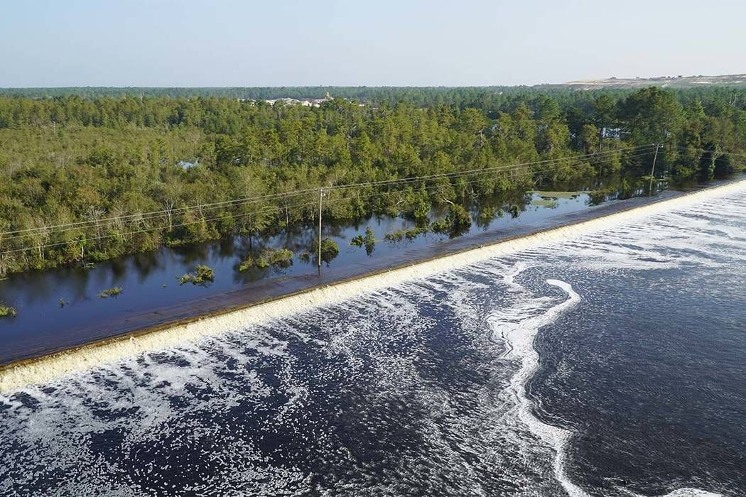 In this drone photo released by Duke Energy, flooding from the swollen Cape Fear River flows over an earthen dike at Sutton Lake, a 1,100-acre lake at the L.V. Sutton Power Station near Wilmington ...