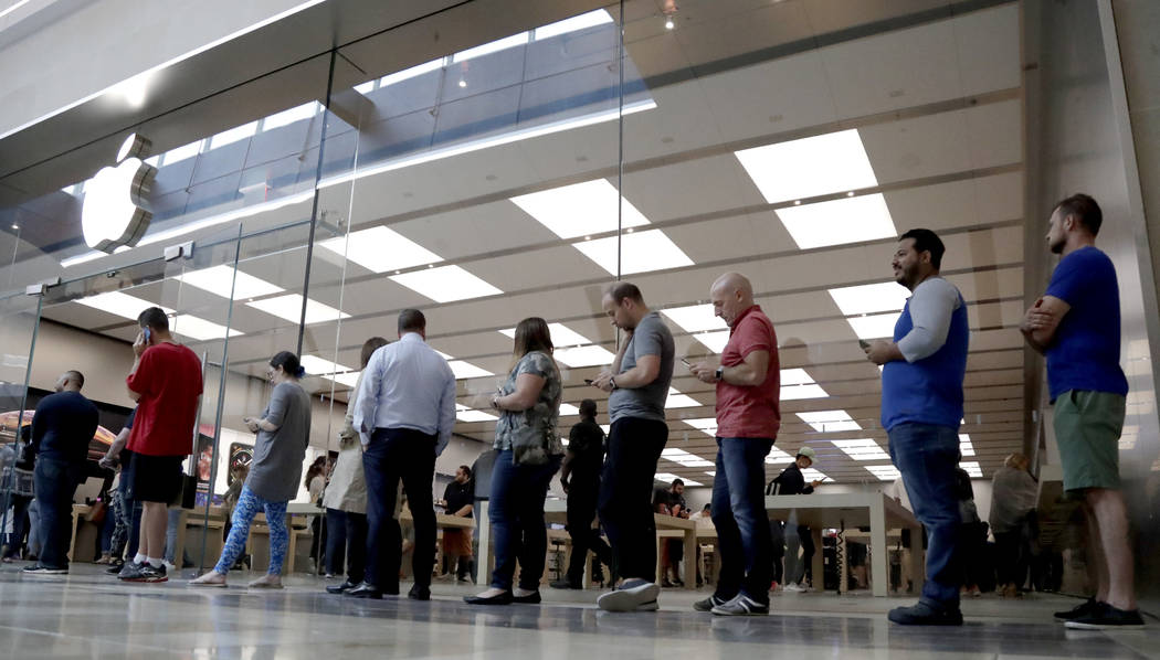 Customers wait in line outside of the Apple Store at the Garden State Plaza on the day the new iPhone XS and iPhone XS Max were released Friday, Sept. 21, 2018, in Paramus, N.J. (AP Photo/Julio Co ...
