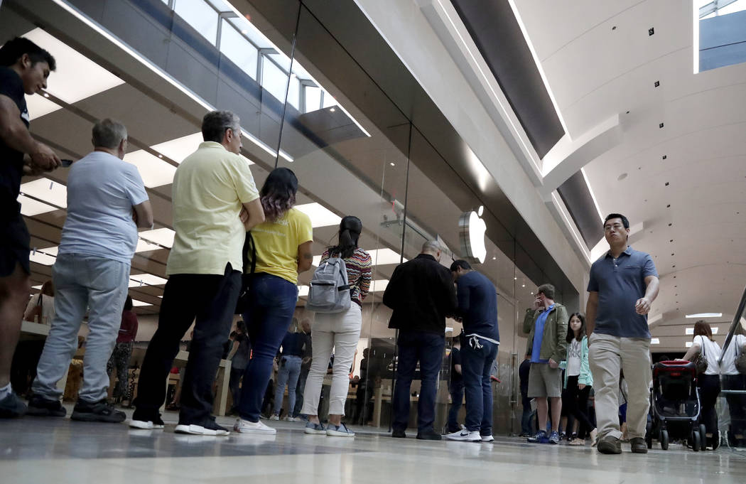 Customers wait in line outside of the Apple Store at the Garden State Plaza on the day the new iPhone XS and iPhone XS Max were released, Friday, Sept. 21, 2018, in Paramus, N.J. (AP Photo/Julio C ...