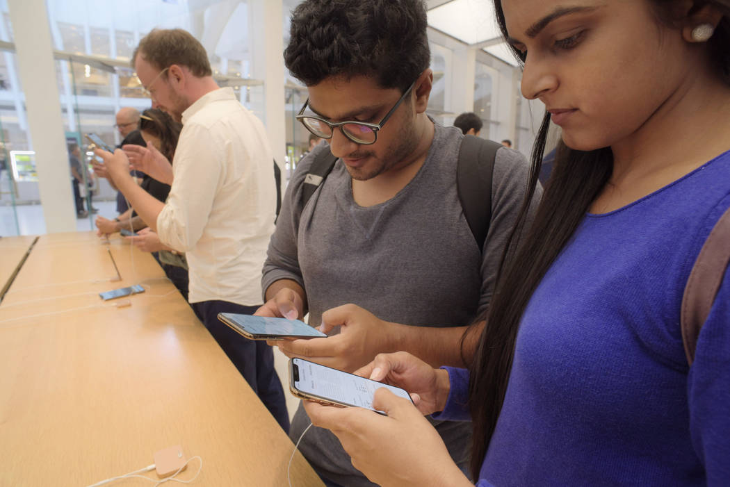Customers look at new Apple iPhones on display including the iPhone XS, front, at an Apple store in New York on Friday, Sept. 21, 2018. (AP Photo/Patrick Sison)