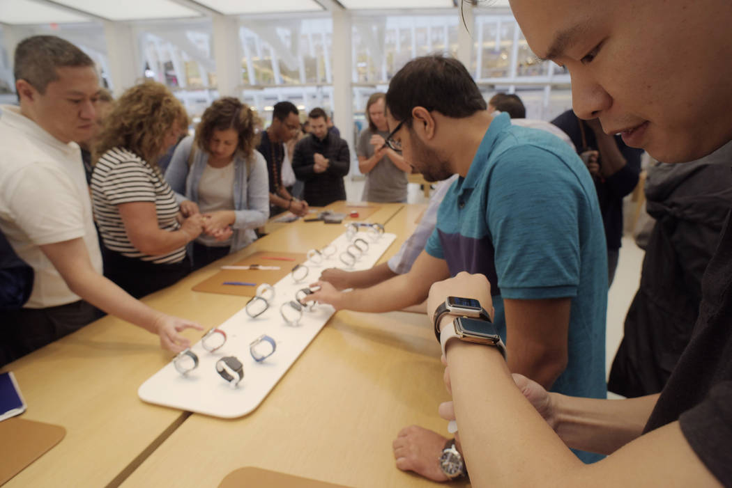 Customers look at new Apple watches including the Series 4 at an Apple store in New York on Friday, Sept. 21, 2018. (AP Photo/Patrick Sison)