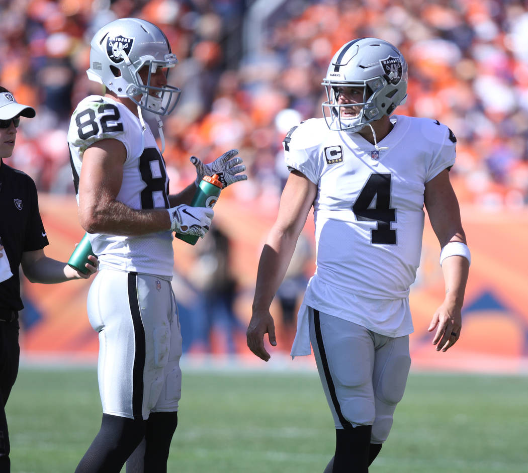 Oakland Raiders quarterback Derek Carr (4) and wide receiver Jordy Nelson (82) talk on the sideline during a timeout the first half of their NFL game against the Denver Broncos in Denver, Colo., S ...