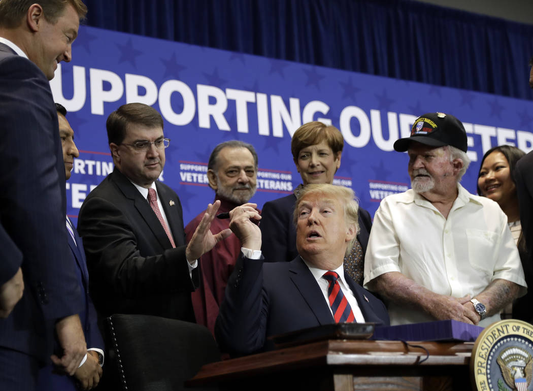 President Donald Trump hands a pen to Veterans Affairs Secretary Robert Wilkie during a spending bill signing ceremony at VA Southern Nevada Healthcare System, Friday, Sept. 21, 2018, in Las Vegas ...