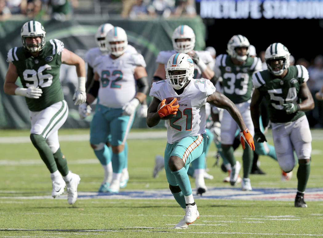 FILE - In this Sunday, Sept. 16, 2018, file photo, Miami Dolphins running back Frank Gore (21) carries the ball against the New York Jets during an NFL football game in East Rutherford, N.J. Runni ...