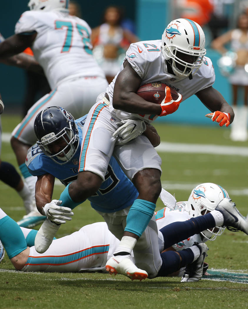 Tennessee Titans linebacker Wesley Woodyard (59) tackles Miami Dolphins running back Frank Gore (21), during the first half of an NFL football game, Sunday, Sept. 9, 2018, in Miami Gardens, Fla. ( ...