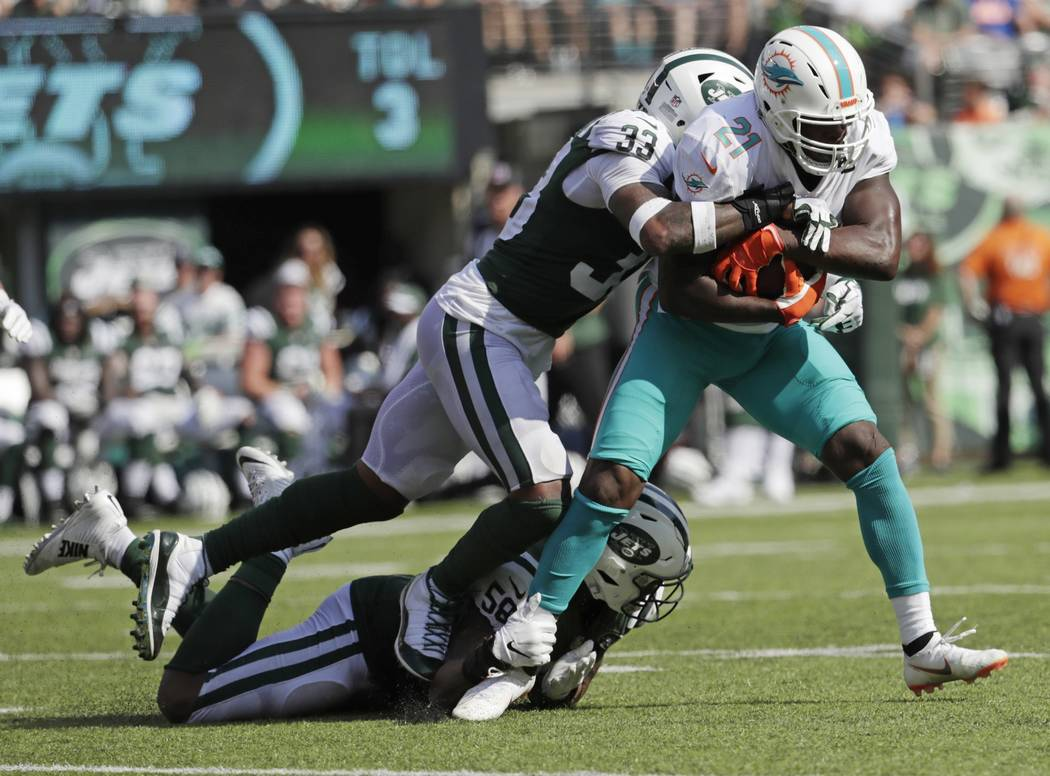 Miami Dolphins' Frank Gore (21) is tackled by New York Jets' Jamal Adams (33) and Darron Lee (58) during the second half of an NFL football game Sunday, Sept. 16, 2018, in East Rutherford, N.J. Th ...