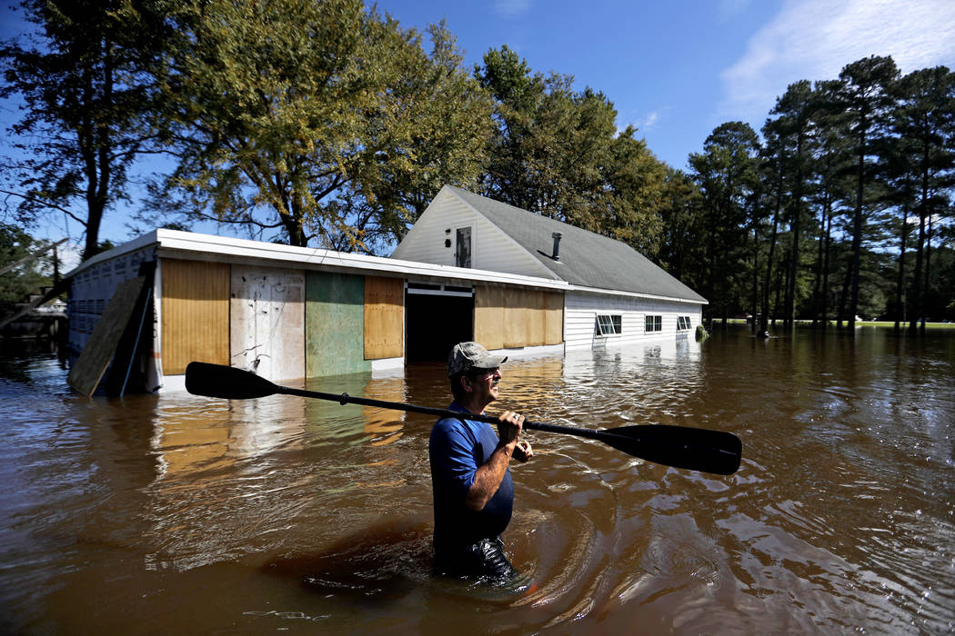 Kenny Babb retrieves a paddle that floated away on his flooded property as the Little River continues to rise in the aftermath of Hurricane Florence in Linden, N.C., Tuesday, Sept. 18, 2018. (AP P ...