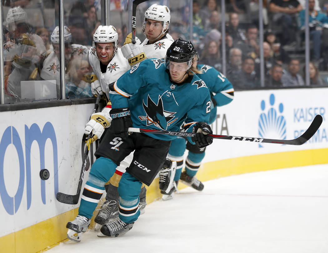 San Jose Sharks left wing Marcus Sorensen (20) checks into the boards Vegas Golden Knights defenseman Jake Bischoff (45) as Nicolas Hague, center, watches during the second period of a preseason N ...