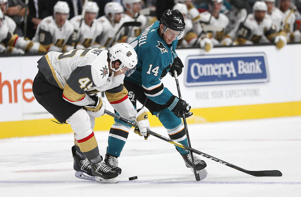 San Jose Sharks center Dylan Gambrell (14) and Vegas Golden Knights defenseman Jake Bischoff (45) vie for the puck during the second period of a preseason NHL hockey game in San Jose, Calif., Satu ...