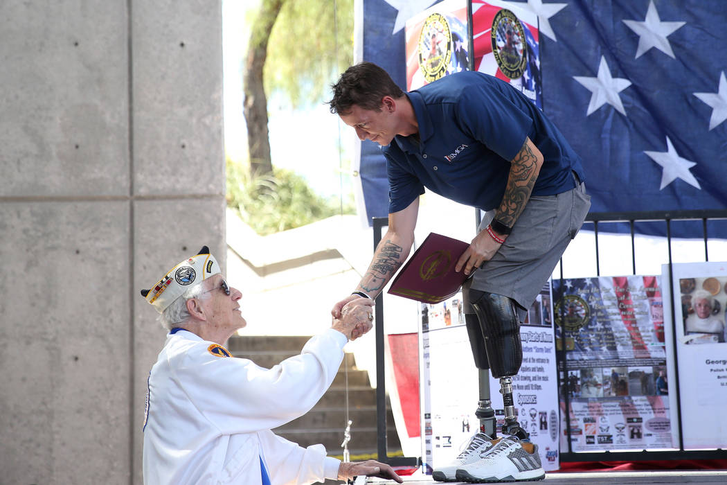 Pearl Harbor Survivor Ed Hall, left, shakes hands with U.S. Army Sgt. Adam Poppenhouse, who was honored during an event by One Hero at a Time at the Henderson Events Plaza in Henderson, Saturday, ...