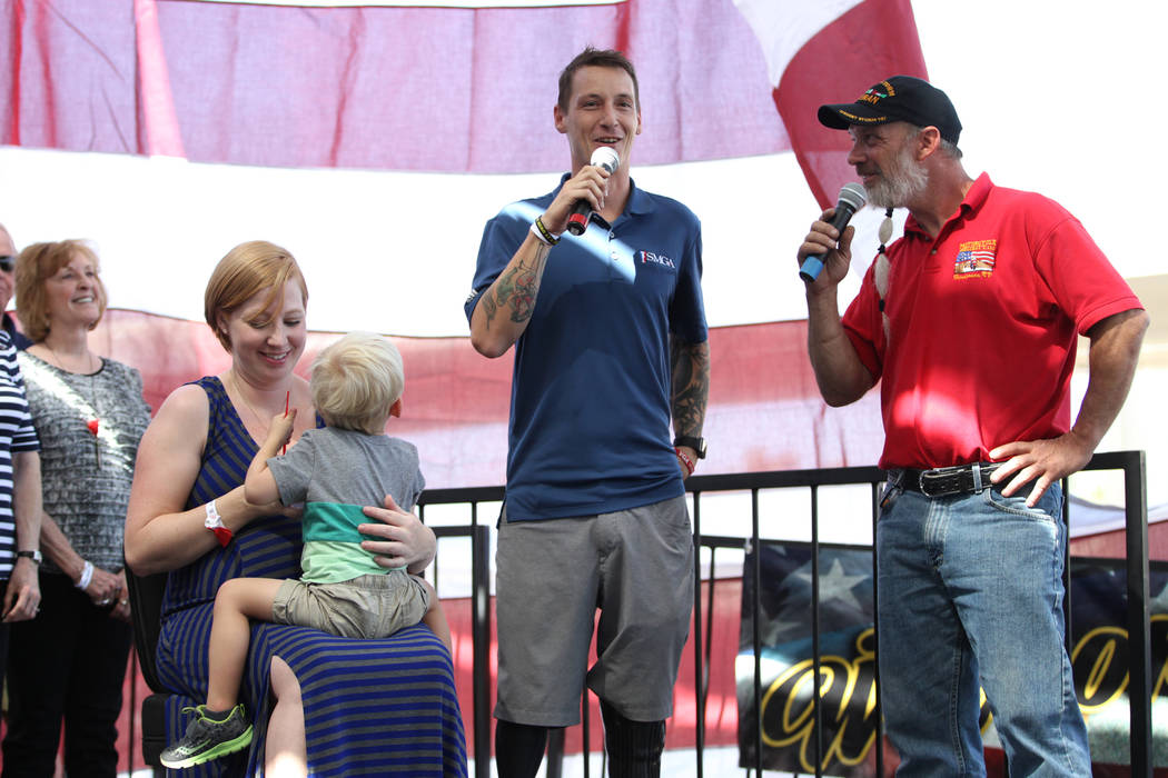 U.S. Army Sgt. Adam Poppenhouse, second from right, with his wife Megan, center, and son Adam Jr., with Rick Hillis, far right founder of One Hero at a Time, is honored during an event at the Hend ...
