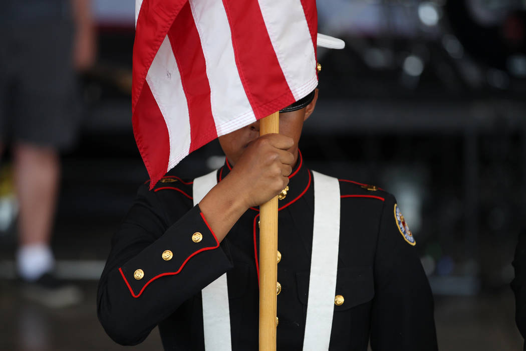 A member of the Basic High School JROTC color guard presents the colors during a One Hero at a Time event honoring U.S. Army Sgt. Adam Poppenhouse at the Henderson Events Plaza in Henderson, Satur ...