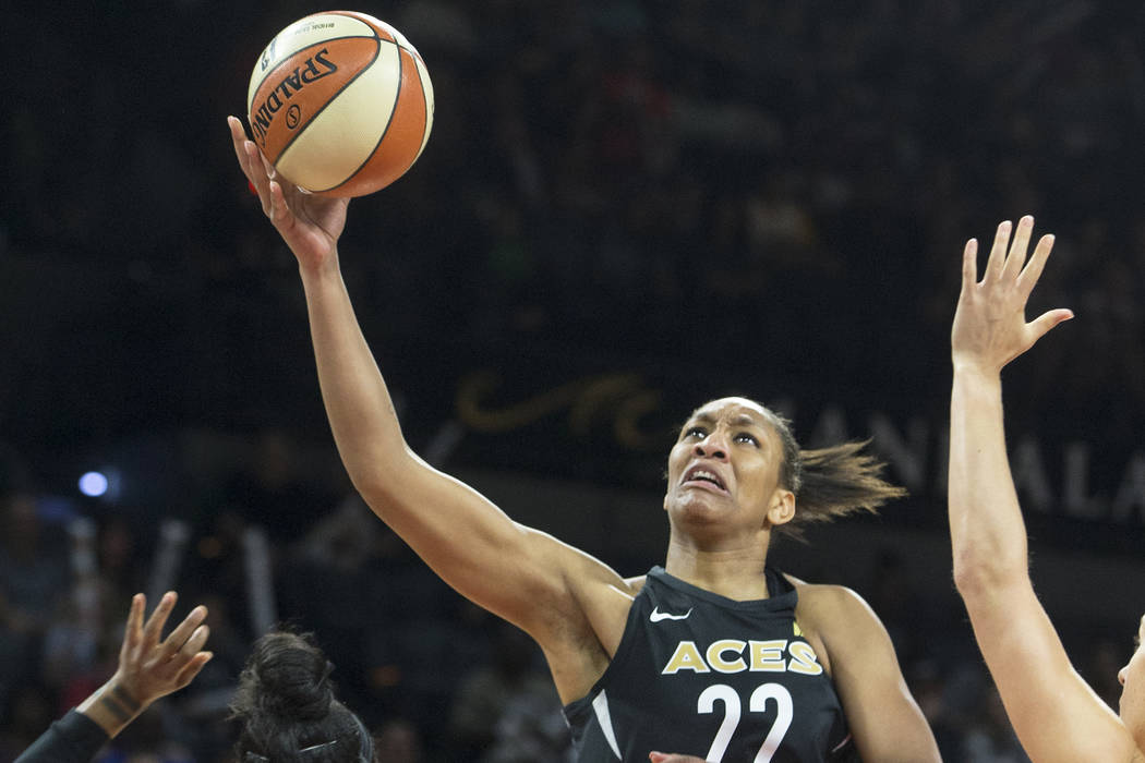 Aces center A'ja Wilson (22) drives past Phoenix Mercury guard Briann January (12) in the first quarter on Wednesday, August, 1, 2018, at the Mandalay Bay Events Center, in Las Vegas. Benjamin Hag ...