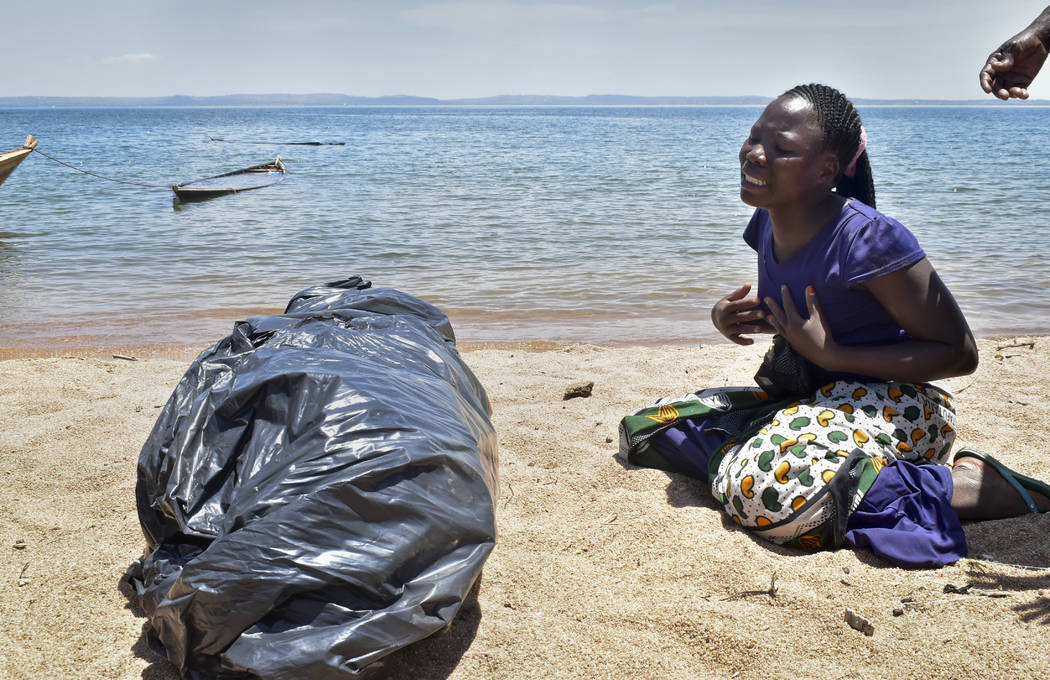 A woman cries beside the body of her sister, a victim of the MV Nyerere passenger ferry, as she awaits transportation for burial on Ukara Island, Tanzania Saturday, Sept. 22, 2018. The death toll ...