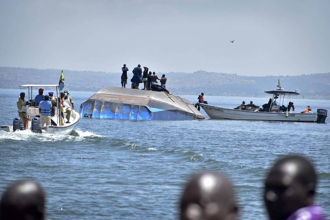 Rescue divers stand on top of the capsized MV Nyerere passenger ferry on Ukara Island, Tanzania Saturday, Sept. 22, 2018. The death toll soared past 200 on Saturday while officials said a survivor ...