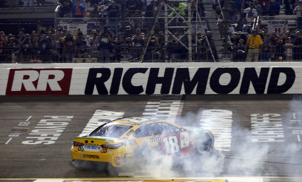 Kyle Busch (18) does a burnout as he celebrates winning the NASCAR Cup Series auto race at Richmond Raceway in Richmond, Va., Saturday, Sept. 22, 2018. (AP Photo/Steve Helber)