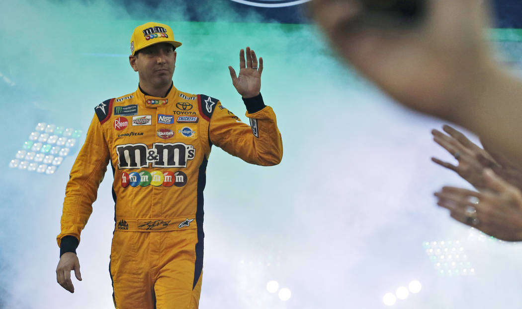 Kyle Busch waves to the crowd during driver introductions prior to the start of the NASCAR Cup Series auto race at Richmond Raceway in Richmond, Va., Saturday, Sept. 22, 2018. (AP Photo/Steve Helber)