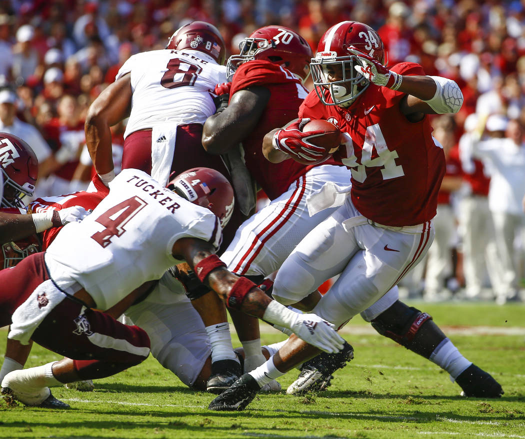 Alabama running back Damien Harris (34) eludes the arms of Texas A&M defensive back Derrick Tucker (4) and carries for first down during the first half of an NCAA college football game, Saturd ...