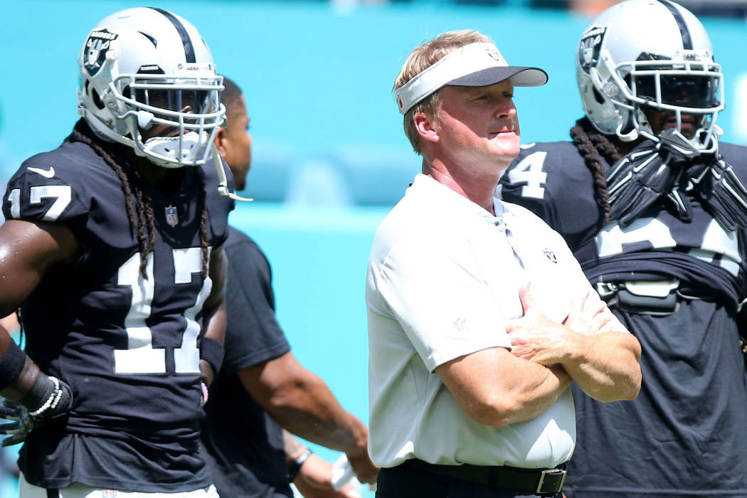 Oakland Raiders head coach Jon Gruden, center, on the field with wide receiver Dwayne Harris (17) and running back Marshawn Lynch (24) prior to their NFL game against the Miami Dolphins in Miami G ...