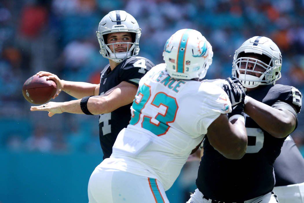 Oakland Raiders quarterback Derek Carr (4) looks to pass the ball as offensive guard Gabe Jackson (66) holds off Miami Dolphins defensive tackle Akeem Spence (93) during the first half of their NF ...