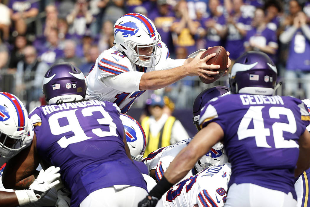 Buffalo Bills quarterback Josh Allen dives into the end zone over Minnesota Vikings' Sheldon Richardson, left, and Ben Gedeon (42) during a 1-yard touchdown run in the first half of an NFL footbal ...