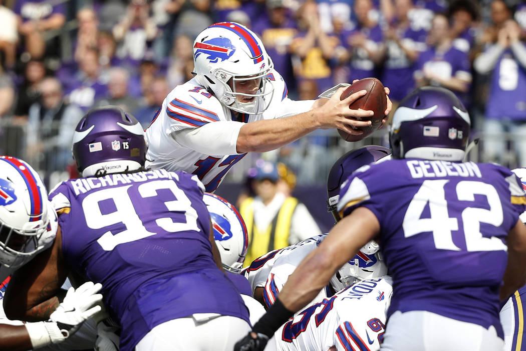 Buffalo Bills quarterback Josh Allen dives into the end zone over Minnesota Vikings' Sheldon Richardson, left, and Ben Gedeon (42) during a 1-yard touchdown run in the first half of an NFL footbal ...