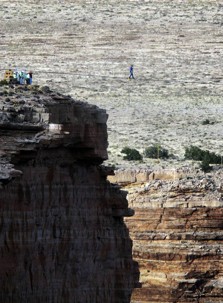 Daredevil Nik Wallenda crosses a tightrope 1,500 feet above the Little Colorado River Gorge, Ariz., on the Navajo Nation outside the boundaries of Grand Canyon National Park, June 23, 2013 (Rick B ...