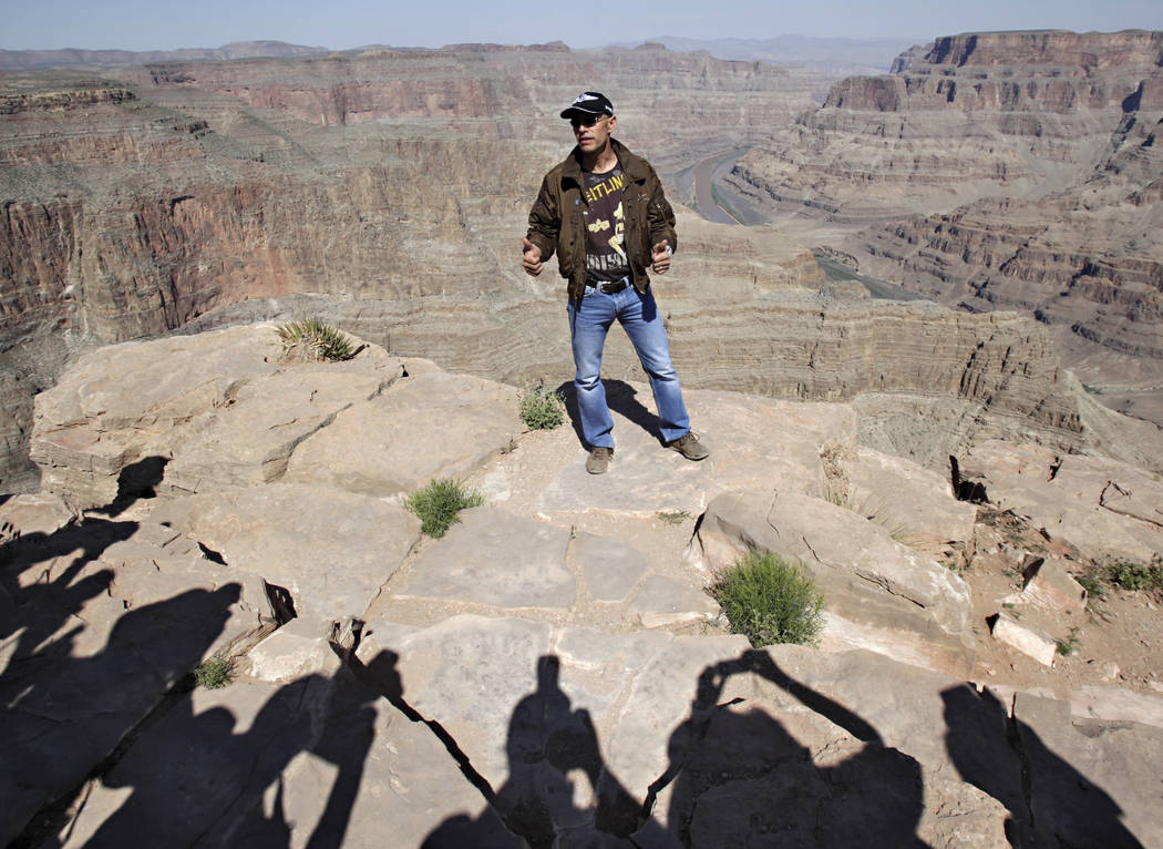 Swiss adventurer Yves Rossy, who calls himself the JetMan, stands on the ledge of the Grand Canyon on Guano Point on the Hualapai Indian Reservation to speak to the media, May 6, 2011. (Matt York/ ...