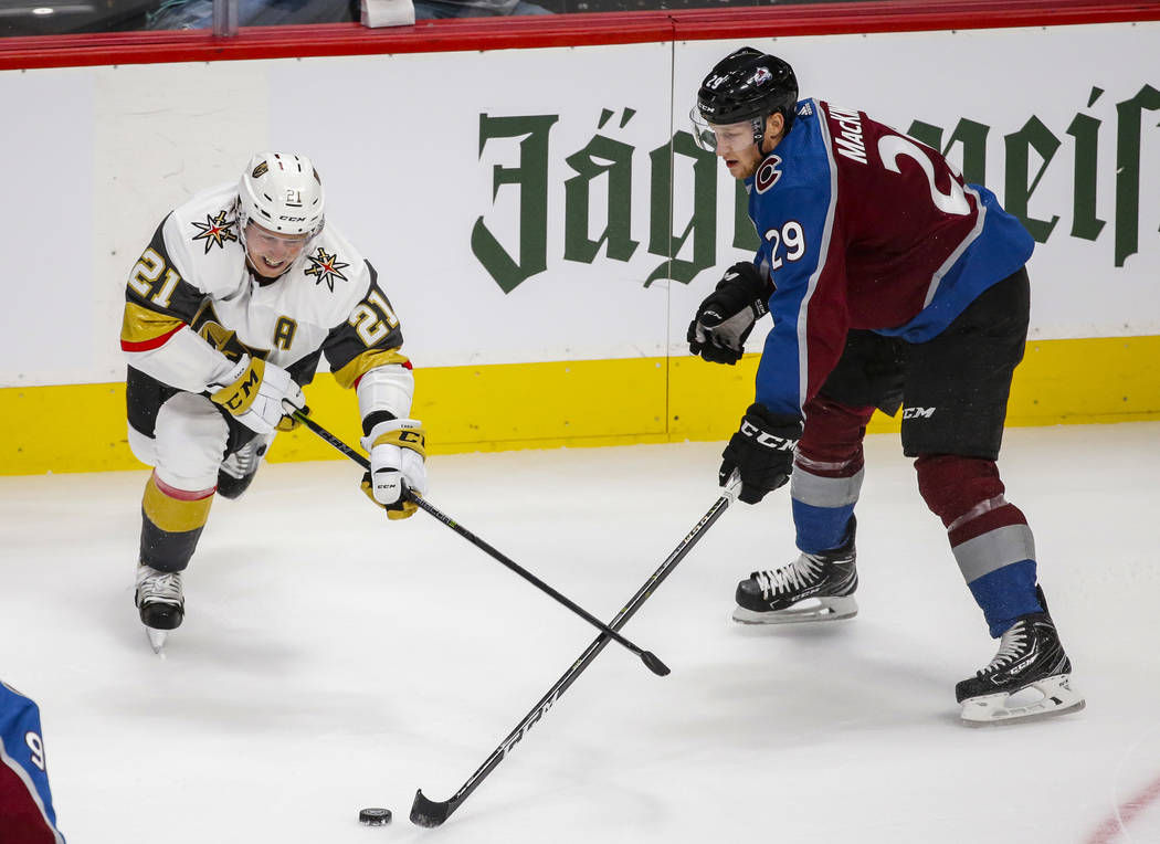 Vegas Golden Knights center Cody Eakin (21) and Colorado Avalanche center Nathan MacKinnon (29) go after the puck during the first period of a preseason NHL hockey game, Tuesday, Sept. 18, 2018, i ...