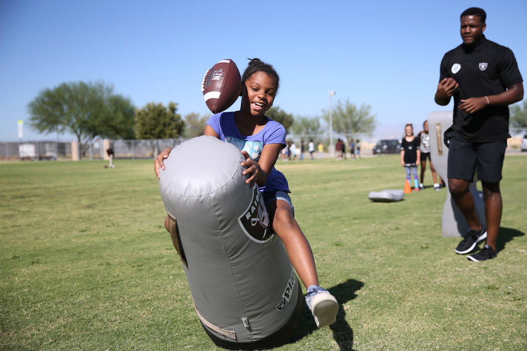 Third grade student Camille Jones, 8, left, participates in a Raiders youth football camp at Robert Taylor Elementary School in Henderson, Tuesday, Sept. 25, 2018. The Raiders adopted a Communitie ...