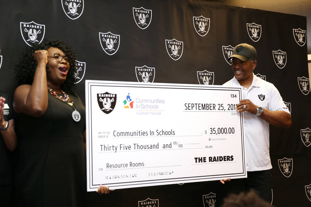 Tiffany Tyler, left, CEO of Communities in School of Nevada, reacts as Raiders alumni Leo Gray presents a donation of $35,000 during an event at Robert Taylor Elementary School in Henderson, Tuesd ...