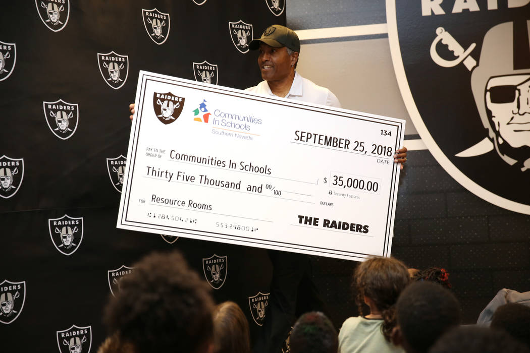 Raiders alumni Leo Gray presents a donation of $35,000 to Communities In Schools of Nevada during an event at Robert Taylor Elementary School in Henderson, Tuesday, Sept. 25, 2018. The Raiders ado ...