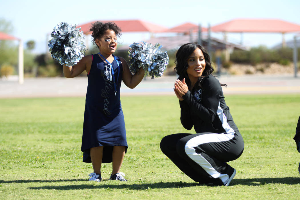 Third grade student Nevaeh Torregano, 8, left, cheers for her classmates with Raiderette Shaniah, during a Raiders youth football camp at Robert Taylor Elementary School in Henderson, Tuesday, Sep ...
