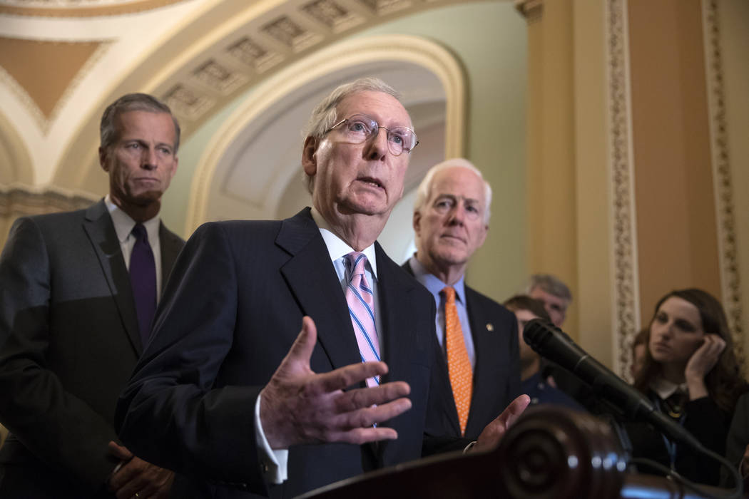 Senate Majority Leader Mitch McConnell, R-Ky., flanked by Sen. John Thune, R-S.D., left, and Majority Whip John Cornyn, R-Texas, speaks with reporters following their weekly policy meetings, at th ...