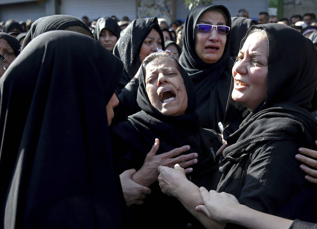 Families of victims of Saturday's terror attack on a military parade in the southwestern city of Ahvaz, that killed 25 people mourn at a mass funeral ceremony, in Ahvaz, Iran, Monday, Sept. 24, 20 ...