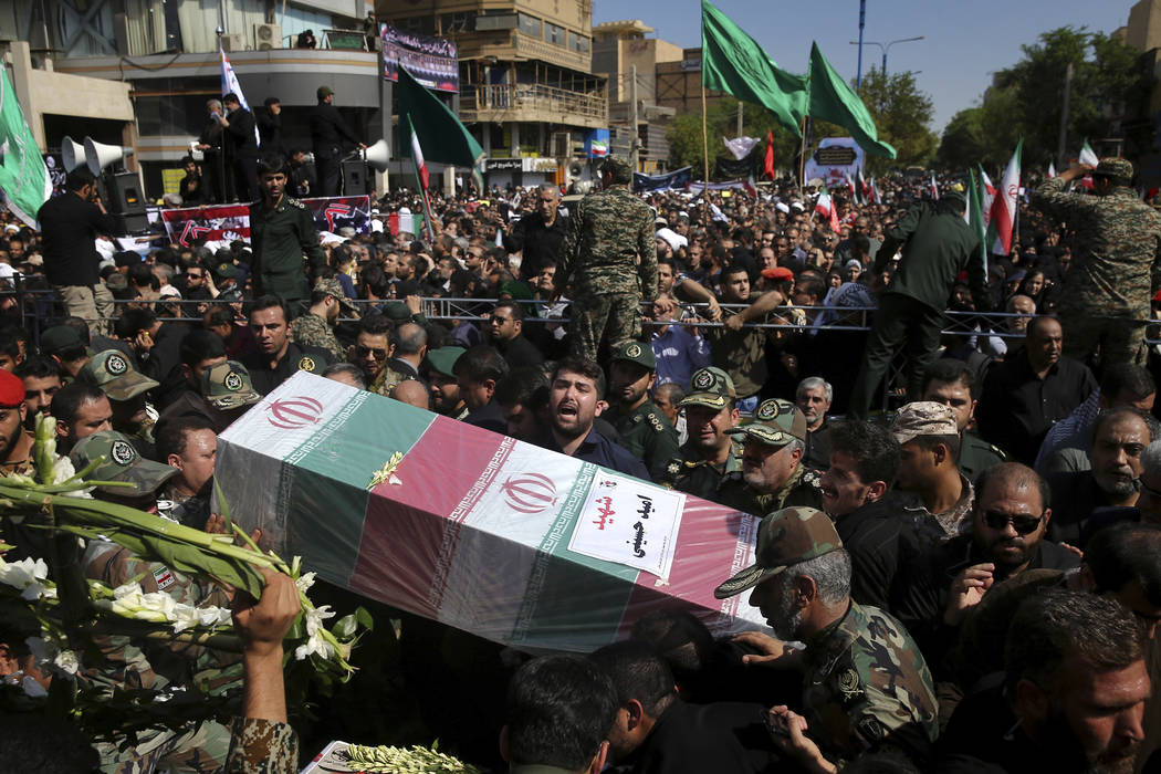 Mourners carry a flag-draped casket during a mass funeral for victims of Saturday's terror attack on a military parade, in the southwestern city of Ahvaz, Iran, Monday, Sept. 24, 2018. Thousands o ...