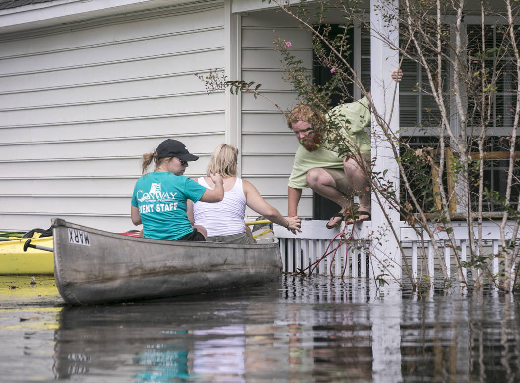 David Covington jumps from a porch railing to his canoe along with Maura Walbourne and her sister Katie Walborne in Conway, S.C., Sunday, Sept. 23, 2018. The three paddled a canoe to Covington's h ...
