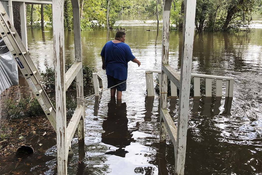 Shawn Lowrimore, Pastor Willie Lowrimore of The Fellowship With Jesus Ministries', son, wades into water near the church in Yauhannah, S.C., on Monday, Sept. 24, 2018. The church is on the bank of ...