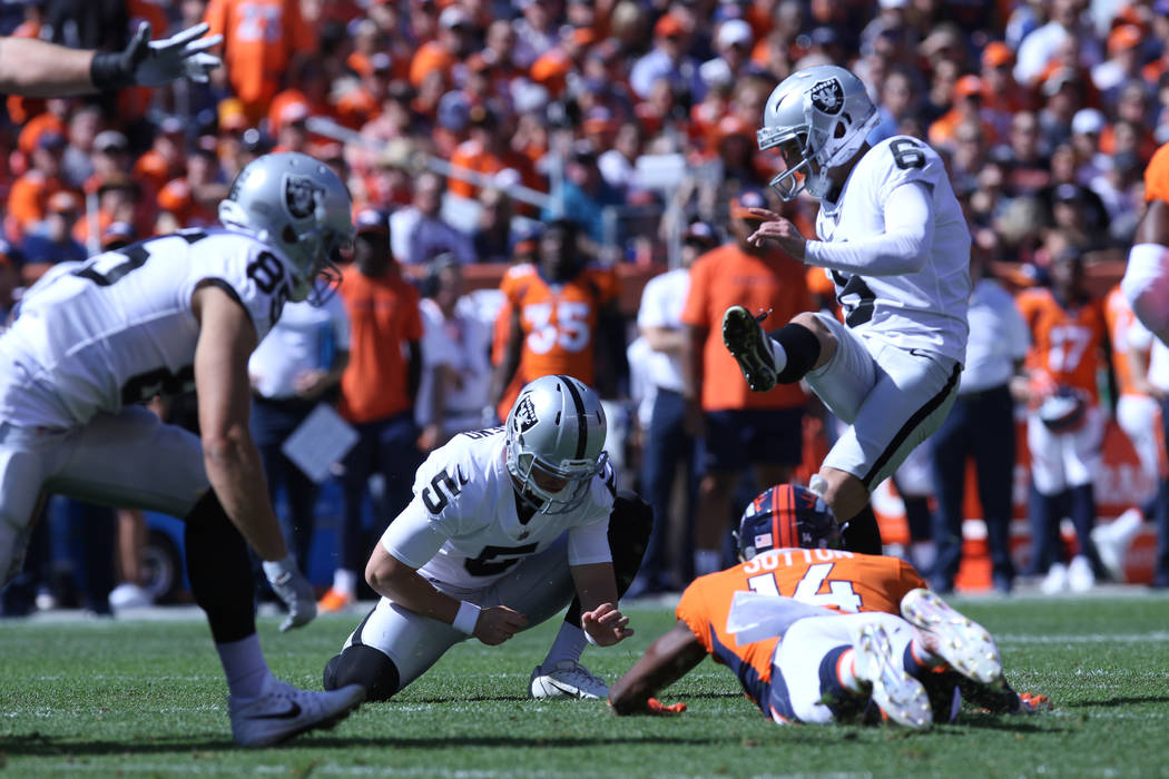 Oakland Raiders kicker Mike Nugent (6) kicks a field goal and punter Johnny Townsend (5) holds as Denver Broncos wide receiver Courtland Sutton (14) comes in for a block during the first half of t ...