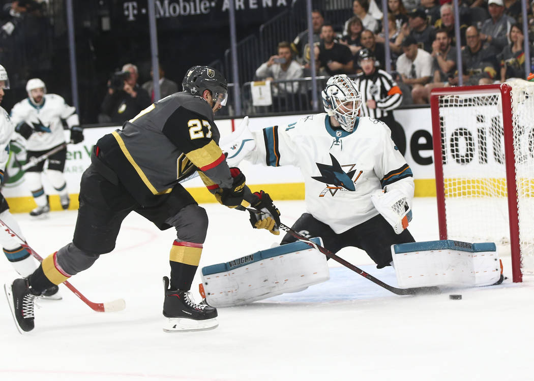 Golden Knights defenseman Shea Theodore (27) tries to get the puck in as San Jose Sharks goaltender Martin Jones (31) defends during the first period of Game 2 of an NHL hockey second-round playof ...