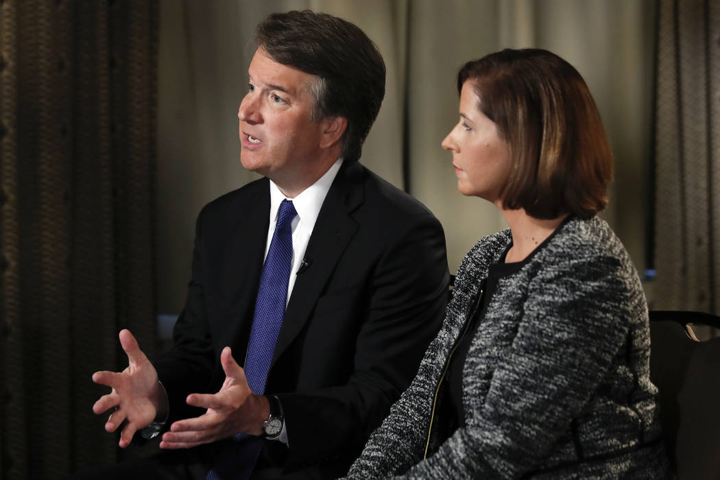 Brett Kavanaugh, with his wife Ashley Estes Kavanaugh, answers questions during a FOX News interview, Monday, Sept. 24, 2018, in Washington, about allegations of sexual misconduct against the Supr ...