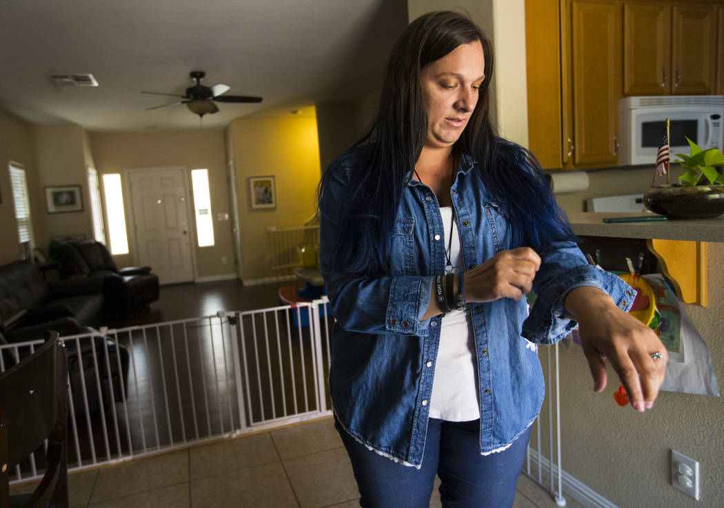 Oct. 1 shooting survivor Teche Bergeron, who was hit by shrapnel while escaping, puts on the denim shirt she wore that night at her home in Las Vegas on Friday, Aug. 17, 2018. Chase Stevens Las Ve ...