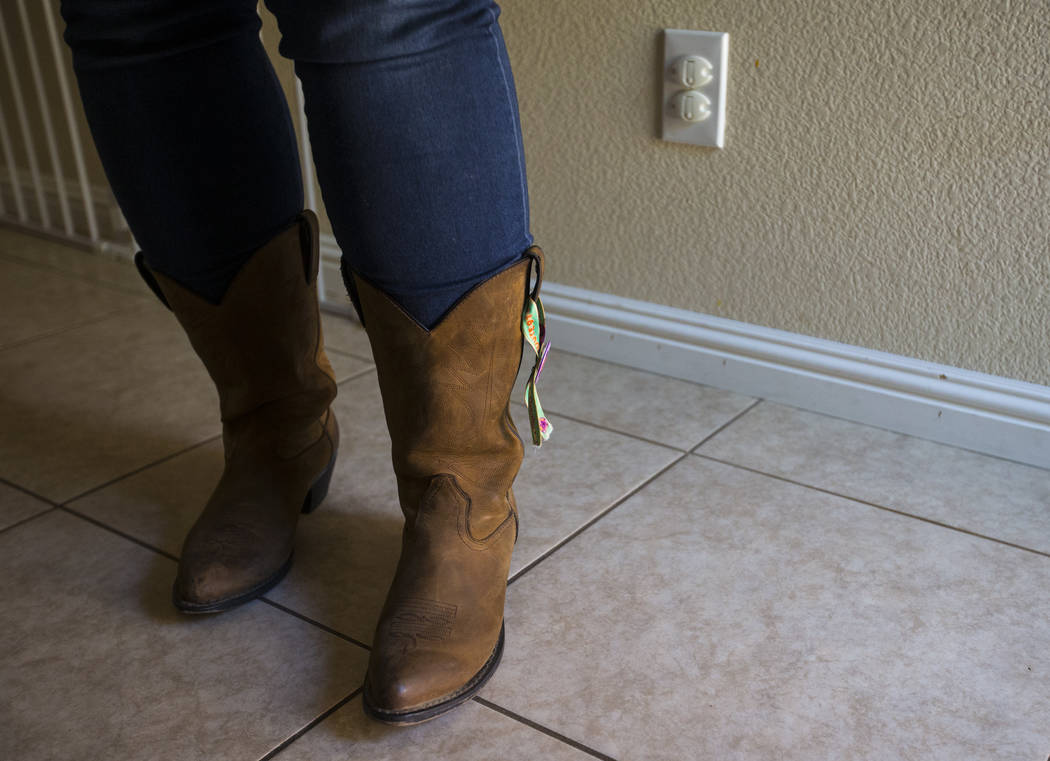 Oct. 1 shooting survivor Teche Bergeron, who was hit by shrapnel while escaping, wears the boots she wore that night at her home in Las Vegas on Friday, Aug. 17, 2018. Chase Stevens Las Vegas Revi ...