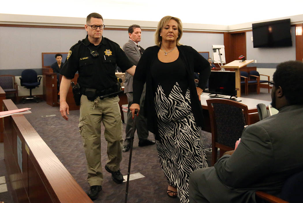 Vicki Greco, right, a suspended Las Vegas attorney who pleaded guilty to three felonies for her role in a scheme to defraud the court system, led out of the courtroom after her sentencing as her d ...