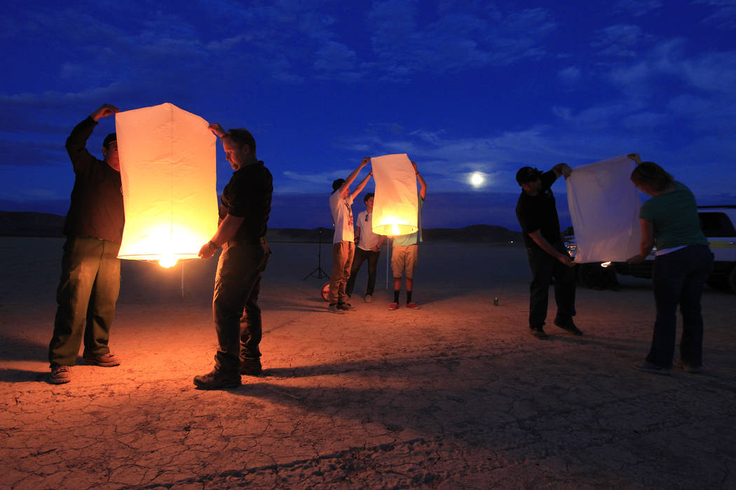 Public lands officials and event organizers fill paper lanterns with heat as they test them and their environmental impact in advance of the RiSE Festival Tuesday, Oct. 6, 2014 on a dry lake bed n ...
